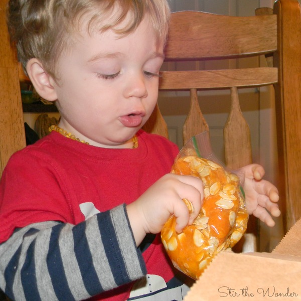 Toddler exploring pumkin guts sensory bag