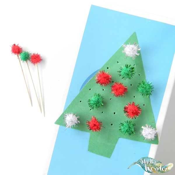 Poking pom pom toothpicks into a Christmas tree is a festive fine motor activity for toddlers and preschoolers.
