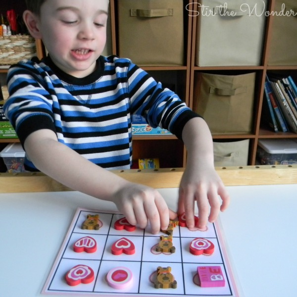 Playing Valentine's Day Grid Math Game with Mini Erasers